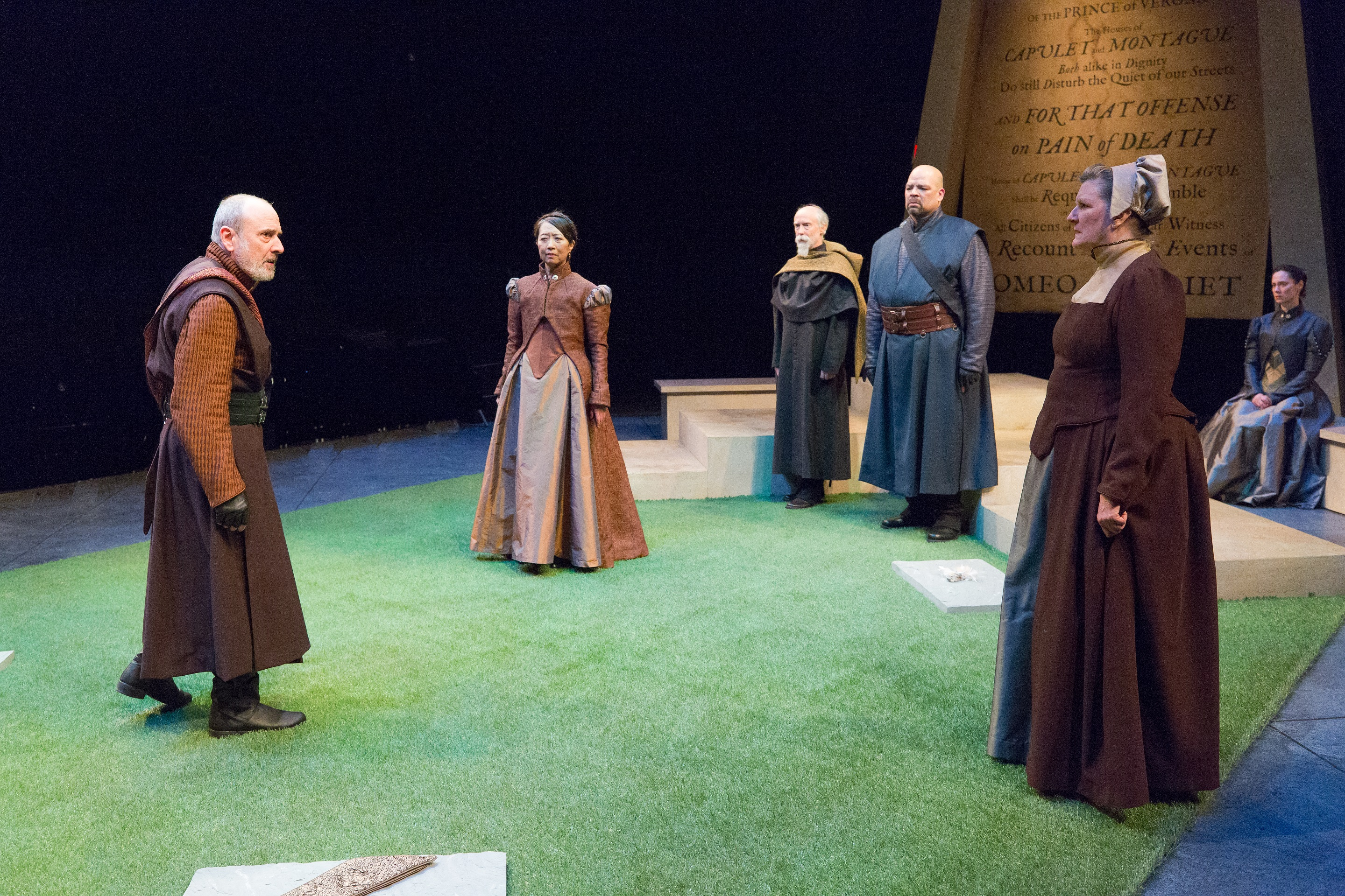 Actors on a green carpeted stage.